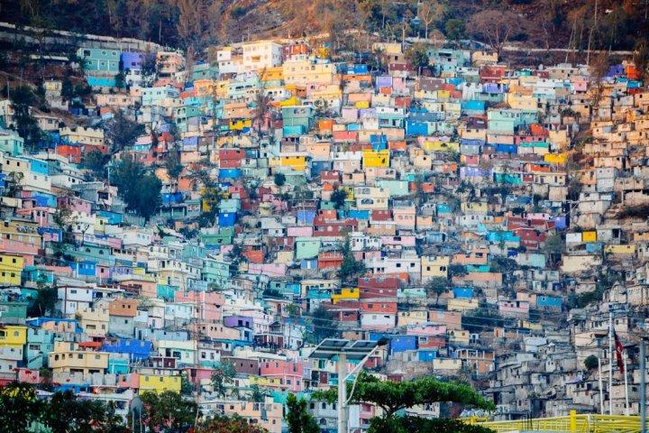 Le quartier de Jalousie. Suspendu au-dessus de Petionville, la banlieue chic de Port-au-Prince, le quartier de Jalousie fait partie des cibles du 16/6. Depuis 2013, ce bidonville de 45 000 habitants a changé radicalement de visage. Les façades d'un millier de maisons ont été repeintes, dans le style des villes imaginaires du peintre haïtien Préfète Duffaut. Et tant pis si des esprits chagrins prétendent que les 1,4 million de dollars de l'opération ont surtout été dépensés pour offrir une vue plus agréable aux riches clients de l'hôtel Oasis, un 5 étoiles juste en contrebas reconstruit après le séisme. (Photo Pierre Morel)