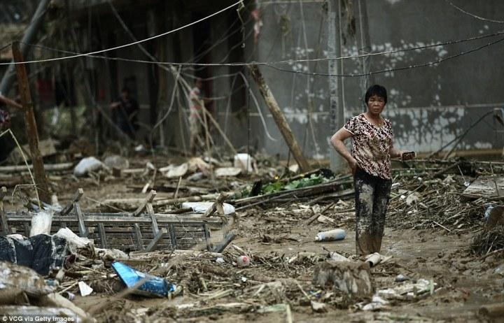 Une résidente parmi les ruines de Bandong ville, dans la province de Fujian en Chine, après le passage du typhon Nepartak - Photo VCG