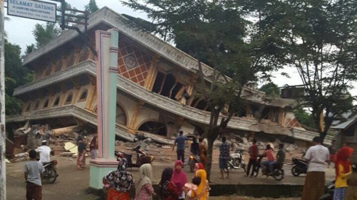 People look at a building that collapsed when an earthquake hit Pidie Jaya regency in Aceh on Wednesday. (Tribunnews.com/File)